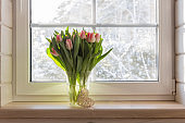 Bouquet of beautiful pink tulips on a wooden windowsill. White window in a Scandinavian style wooden house overlooking the garden, pine forest. Spring concept, Happy 8 March, Women's Day