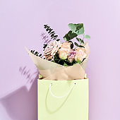 Happy Mothers day. Beautiful and fresh flowers bouquet in paper gift bag over purple background