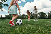 Closeup of little girl kicking the ball while parents watching. Young family playing football on the grass field in the park on a summer day