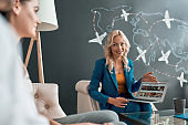 Attractive female travel agent looking at her clients, communicating with them in office and showing tours, using laptop