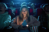 Beautiful young woman smiling, using her phone for texting while watching a movie at the cinema