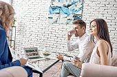 Young couple sitting at tourist agency, drinking coffee and listening to female travel agent while preparing for vacation