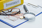 Clean insurance form, magnifying glass and money