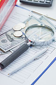 Clean insurance form, magnifying glass, pen and money