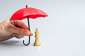 Business man hand holding red Umbrella cover Chess King figure. Business, Risk Management, Solution, economic regression, Insurance, strategy and Interruption Concepts