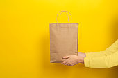 Female hands hold large gift bag made of brown craft paper on yellow background.