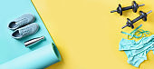 Banner of sport and fitness equipment, yoga mat, shoes, water bottle on yellow. Top view, space for your text.