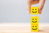 Hand holding smile face symbol on yellow wooden cube blocks. Emotion, Service rating, ranking, customer review, satisfaction and feedback concept
