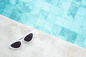 white sunglasses near swimming pool in luxury hotel. Summer travel, vacation, holiday and weekend concept