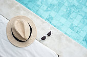 white sunglasses and hat near swimming pool in luxury hotel. Summer travel, vacation, holiday and weekend concept