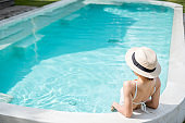 Happy woman in white swimsuit swimming in luxury pool hotel, young female with hat enjoy in tropical resort. Relaxing, summer travel, holiday, vacation and weekend concept
