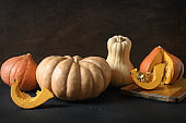 Organic pumpkins on beige background. Autumn harvest for Thanksgiving Day or Halloween Party.