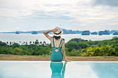 Happy woman in green swimsuit swimming in luxury pool hotel against ocean nature background, young female with hat enjoy in tropical resort. Relaxing, summer travel, holiday, vacation concept