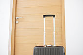 Black Luggage near the door in modern hotel room. Time to travel, business, service, journey, trip, summer holiday and vacation concepts