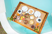Floating Breakfast tray in swimming pool at luxury hotel or tropical resort villa, fruits, croissant, coffee, and orange juice. Exotic summer, relaxation, tropical travel and vacation concept