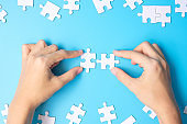 hands connecting couple white puzzle jigsaw pieces on blue background. Concept of solutions, mission, success, goals, cooperation, partnership, strategy and puzzle day