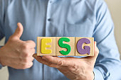 Wooden cube blocks with the abbreviation ESG in hands.