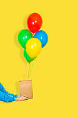Female hands hold the paper bag and a bunch of balloons. Sale or present concept. Green, red, yellow, and blue Balloons, brown paper bag and hands isolated on yellow background