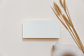 Wedding  mock-up. Blank greeting card and green palm leaves. Ceramic vase on beige neutral background. Flat lay, top view. Mediterranean, summer design.