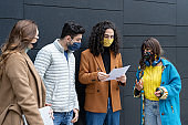group of university students talking to each other with facial masks for personal protection from Corona Virus