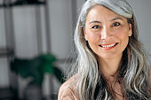 Close-up portrait of happy successful influential senior gray-haired Asian business woman, top manager, lawyer, real estate agent, standing at office, in stylish wear, looks at camera, smiles friendly