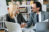 Influential business partners discussing about new start-up in modern office. Successful coworkers are sitting at the work desk, using laptop. Clever senior man gives advices beautiful woman on working process
