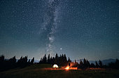 Hiker standing near campfire under night starry sky.
