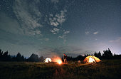 Hikers standing near campfire under beautiful starry sky.
