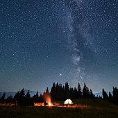 Hiker sitting near campfire under night starry sky.
