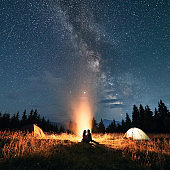 Young couple sitting near campfire under beautiful starry sky.