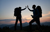 Silhouettes of couple of travelers in the mountains at sunset.