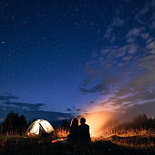 Young couple sitting near campfire under cloudy night sky.