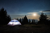 Beautiful night view of starry sky over camping in the mountains.