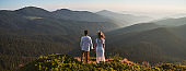 Young couple in love standing on grassy hill in mountains.