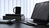 Close up view of computer tablet, books calculator and coffee cup on dark modern office desk.