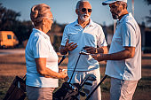 Senior friends on golf court talking.