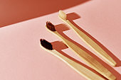 Reusable bamboo toothbrushes on pink background. Zero waste