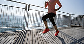 Healthy lifestyle fitness sports woman runner running on seaside trail