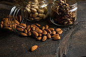 Almonds scattered on the wooden vintage table from a jar. Almond is a healthy vegetarian protein nutritious food. Almonds on rustic old wood.