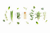Essential oil and mix of herbs, green branches, leaves eucalyptus, aloe Vera, rosemary, thyme on white background. Flat lay. Top view