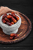 Bowl of dried dates on dark wooden background