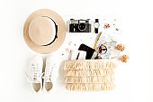 Woman fashion travel. Straw hat, bag with accessories, sneakers, retro camera, sunglasses. Flat lay. Top view