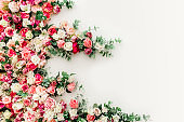 Flower pattern made of pink, beige roses flower buds on white background. Flat lay, top view