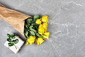 Yellow roses in craft paper and trendy gift box in recycled paper on gray background. Natural aestetic. Valentines day,Mothers day,Womens day flat lay