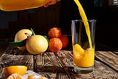 Fresh squeezed orange juice poured into a glass on wooden background.Healthy eating,detox,dieting and vegetarian concept