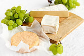 Delicious cheese brie or camembert on cutting board with bunch of grape on the table with white tablecloth. Dairy products. Italian, French cheese. Breakfast. Selective focus