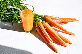 Glass of fresh squeezed carrot juice on the table of the kitchen. Healthy eating, detox, dieting and vegetarian concept