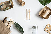 Composition with disposable paper and reusable tableware with natural leaves.