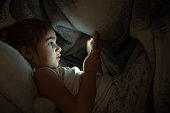 Cute little girl uses phone in bed at night instead of sleeping close up.