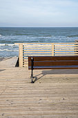 Beautiful view of wavy sea on a sunny day with terrace and wooden bench.